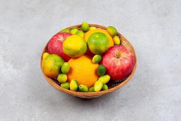 Schließen sie herauf foto des obstkorbs. frische früchte im korb über grauer oberfläche.