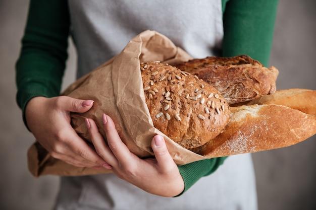 Schließen sie herauf foto des weiblichen bäckers, der tasche mit brot hält