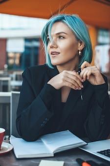 Schließen sie herauf foto einer kaukasischen frau mit blauen haaren, die über etwas wichtiges nachdenken, während sie einen laptop und ein buch in einer cafeteria verwenden