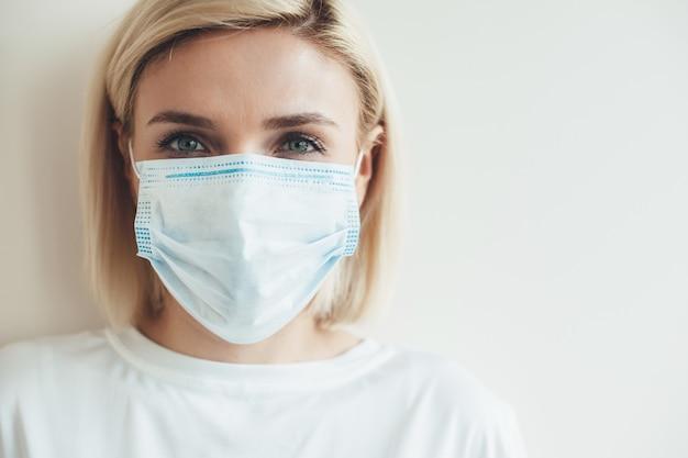 Schließen sie herauf foto einer kaukasischen frau mit medizinischer maske und blondem haar nahe weißem freiem raum