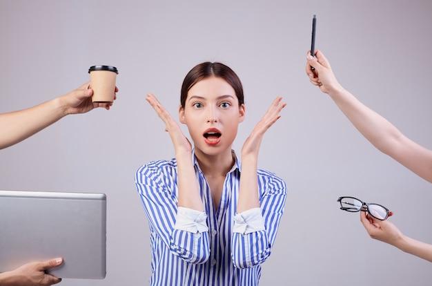 Schließen sie herauf foto eines frauenmanagers in einem gestreiften weiß-blauen hemd mit gläsern auf grau. mitarbeiterin des jahres, business lady. die hände reichen der frau einen laptop, einen stift, eine brille und eine tasse kaffee.