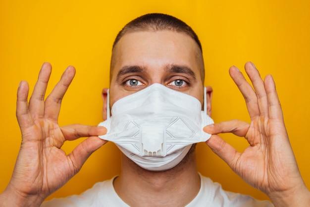 Schließen sie herauf foto eines jungen bärtigen weißen mannes mit einer medizinischen gesichtsmaske während der coronavirus-quarantäne. der vordere teil des gesichts war leicht verschwommen. coronavirus, covid-19-ausbruch. doktor, krankenschwester konzept.