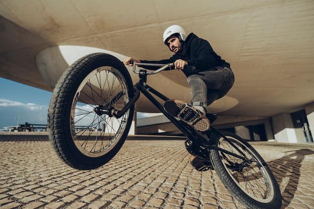 Schließen sie herauf foto eines mannes, der einen wheelie vor der kamera tut.
