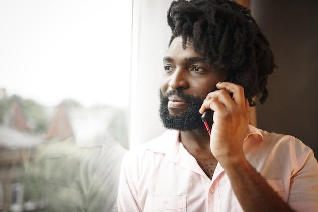 Schließen sie herauf foto eines schwarzen mannes mittleren alters im formellen hemd, das auf seinem telefon nahe dem fenster spricht