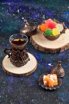 Schließen sie herauf foto von bunten bonbons und duftendem tee auf holzbrett