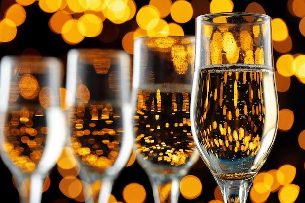 Schließen sie herauf foto von champagnergläsern gegen bokehlichter