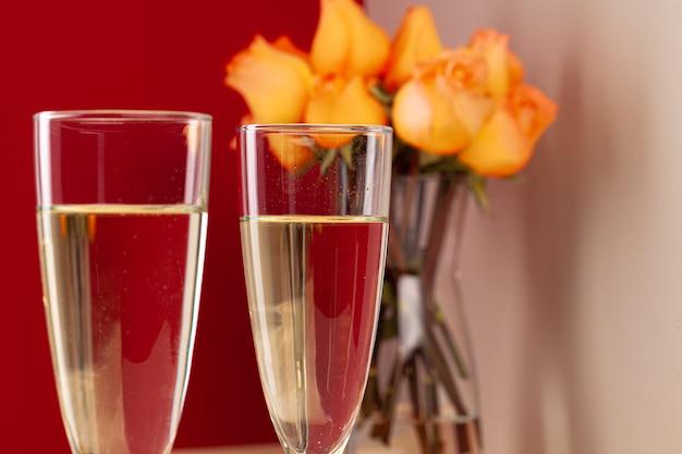 Schließen sie herauf foto von champagnergläsern mit rosen in einer vase