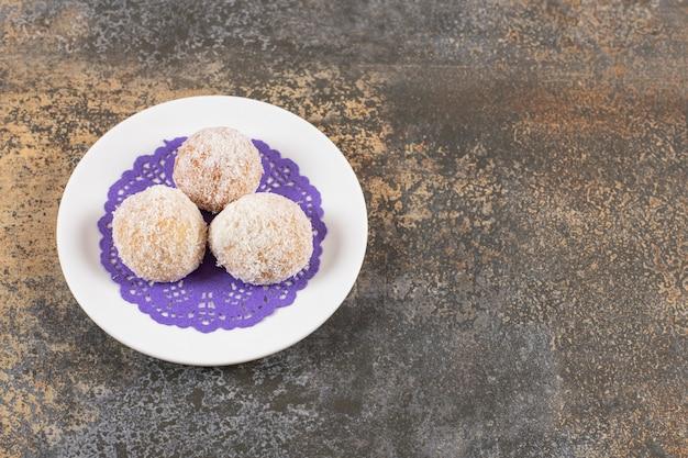 Schließen sie herauf foto von drei frischen hausgemachten keksen auf weißem teller.