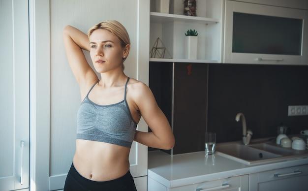 Schließen sie herauf foto von einem kaukasischen blonden mädchen, das sich in der küche vor yoga lektionen wärmt