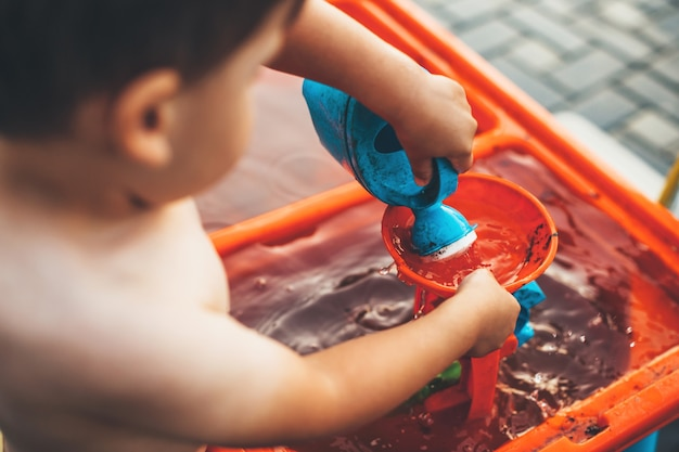 Schließen sie herauf foto von einem kaukasischen jungen, der draußen mit wasser und plastikspielzeug spielt, das in der backyad ausgezogen wird
