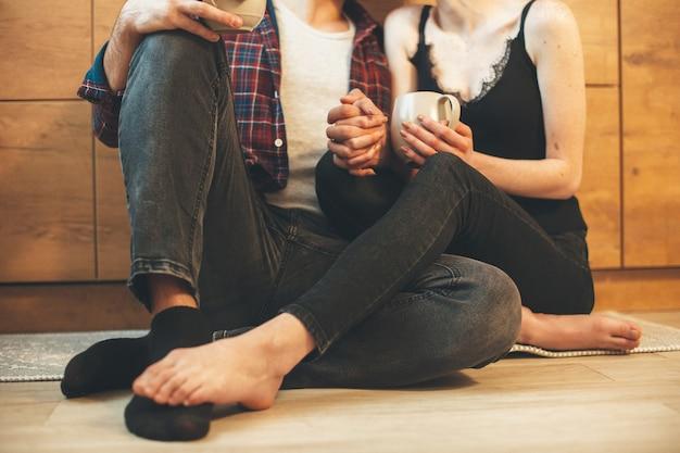 Schließen sie herauf foto von einem kaukasischen paar, das auf dem boden sitzt, der hand in hand posiert, während eine tasse tee hält