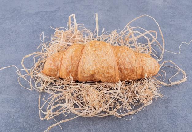 Schließen sie herauf foto von frischem französischem croissant auf stroh über grauem hintergrund.