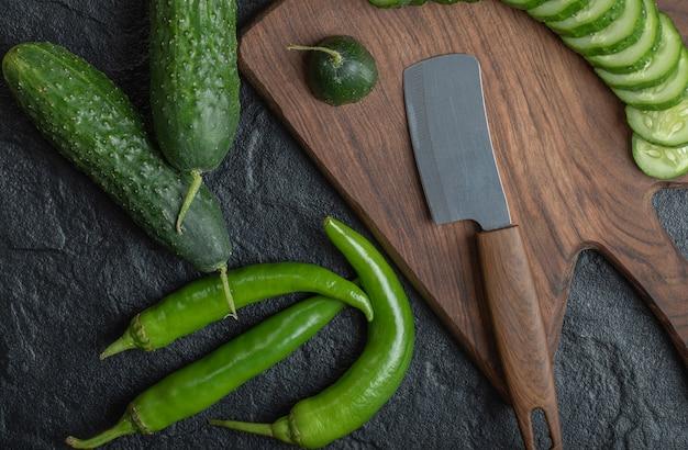 Schließen sie herauf foto von geschnittener gurke und scharfen grünen paprikaschoten. hochwertiges foto