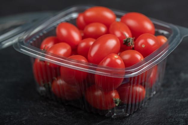 Schließen sie herauf foto von kleinen frischen tomaten im plastikbehälter. hochwertiges foto