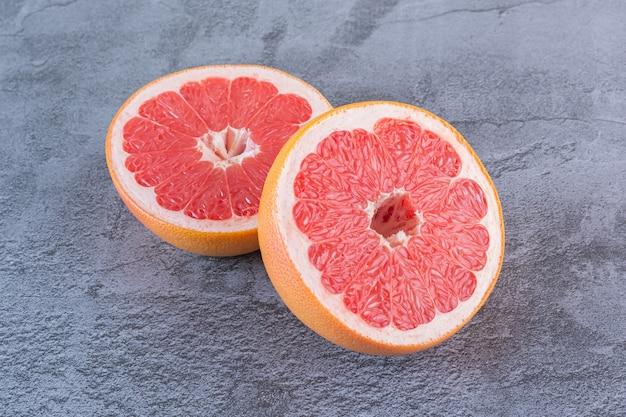 Schließen sie herauf foto von saftigen grapefruitscheiben auf grau.