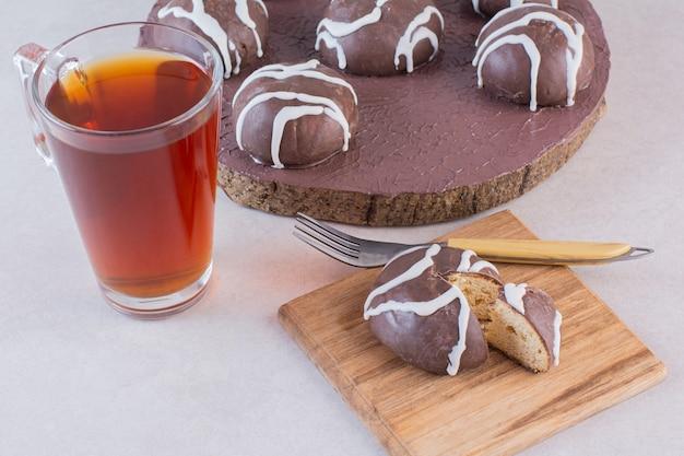 Schließen sie herauf foto von schokoladenplätzchen mit tee auf grau