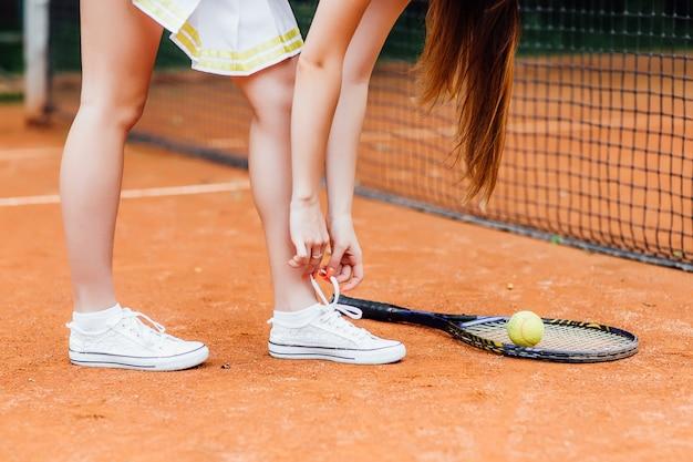 Schließen sie herauf foto von sportlichen frauenbindungsspitzen auf tennisplatz. gesundes leben.