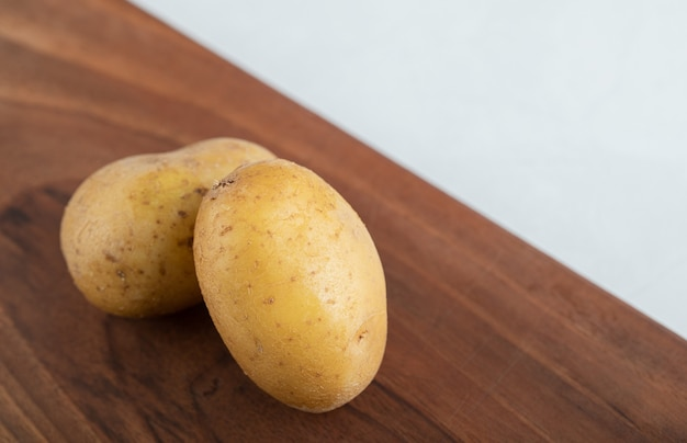 Schließen sie herauf foto von zwei frischen kartoffeln auf braunem holzbrett