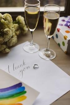 Schließen sie herauf foto von zwei gläsern mit champagner, postkarte, ehering und lgbt zeichen lokalisiert