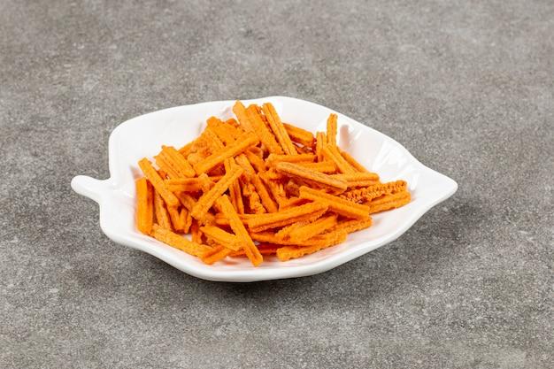 Schließen sie herauf foto weiße platte auf grau voll mit chips.