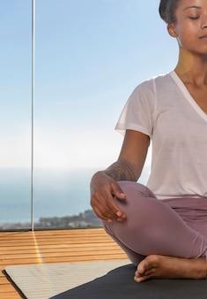 Schließen sie herauf frau, die auf yogamatte sitzt