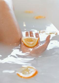Schließen sie herauf frau, die mit orangenscheiben im wasser badet