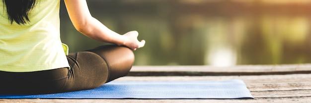 Schließen sie herauf frau, die yoga praktiziert, das yoga im morgenpark tut