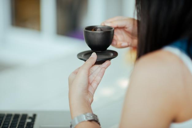 Schließen sie herauf frau mit schalenkaffee im café