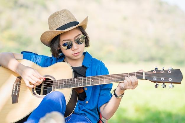 Schließen sie herauf frauenabnutzungshut und gitarre spielen