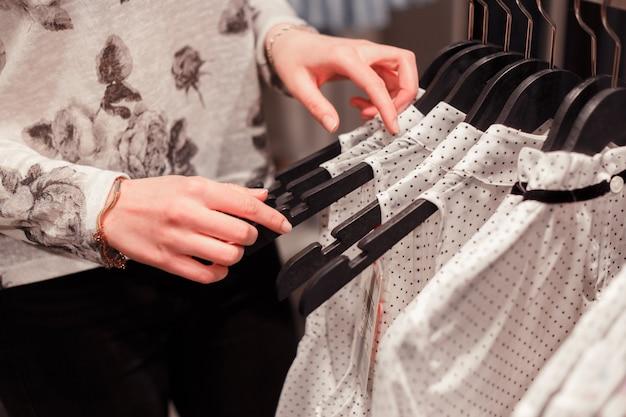 Schließen sie herauf frauenhände auf kleiderbügeln in einem speicher, der nach passender größe sucht.