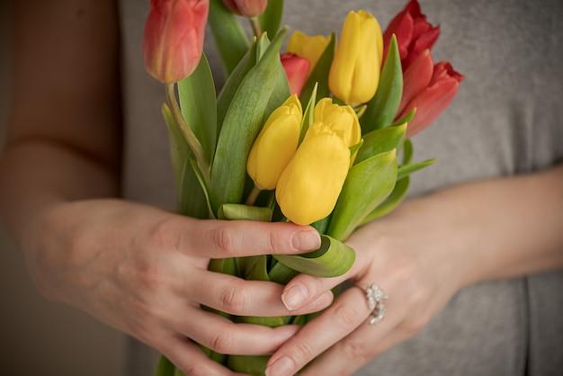 Schließen sie herauf frauenhände, die bündel tulpenblumen halten