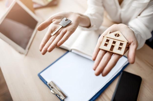 Schließen sie herauf frauenhände, die schlüssel und holzhaus halten. dokumentiert tablet und telefon auf dem tisch.