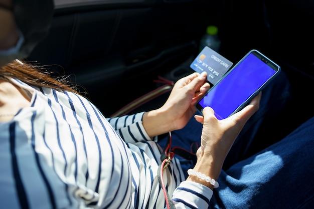 Schließen sie herauf frauenhände, die smartphone und kreditkarte halten, während sie auf dem rücksitz des autos sitzen.