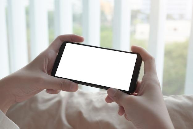 Schließen sie herauf frauenhand, die ein smartphone mit leerem bildschirm zu hause verwendet.