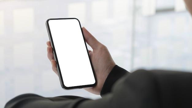 Schließen sie herauf frauenhand, die ein smartphone mit weißem bildschirm zu hause verwendet.