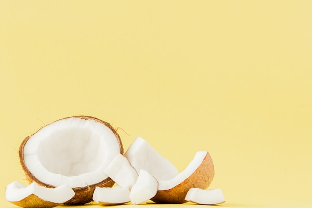 Schließen sie herauf frische kokosnussstücke lokalisiert auf gelbem hintergrund, tropisches fruchtkonzept, flache lage, pop-art, kopienraum.