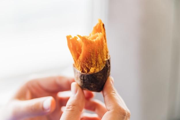 Schließen sie herauf gebackene süßkartoffel mit schale in den händen, die in taiwan, taipeh heiß und süß sind.