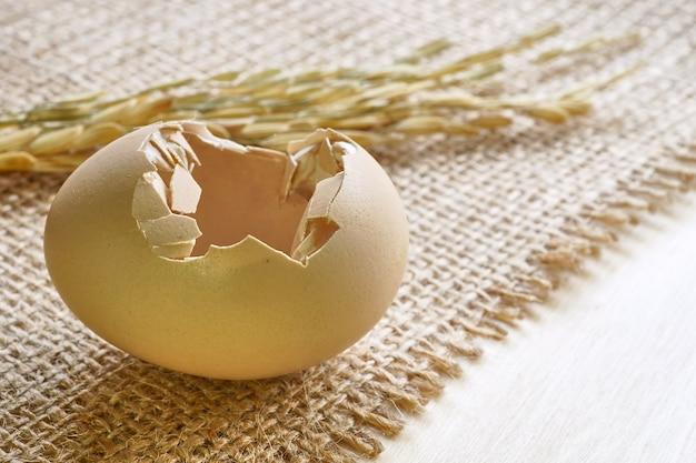Schließen sie herauf gebrochenes ei auf sackstoff mit undeutlichem reis auf hintergrund