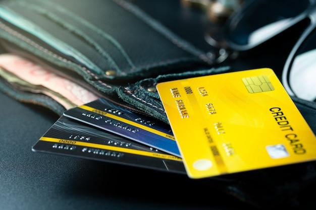 Schließen sie herauf gelbe kreditkarte auf geldbörsenhintergrund
