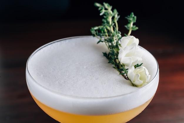 Schließen sie herauf gelbes cocktail mit dem weißen schaum, der mit weißer blume und grüner niederlassung verziert wird. studioaufnahme.