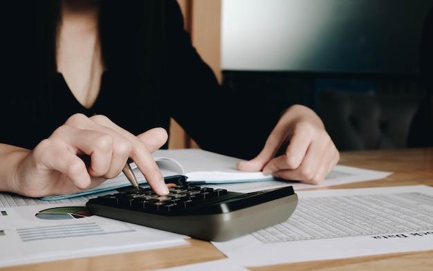 Schließen sie herauf geschäftsfrau, die taschenrechner und laptop für mathematische finanzen auf holzschreibtisch in büro- und geschäftsarbeit, steuer-, buchhaltungs-, statistik- und analytischem forschungskonzept verwendet