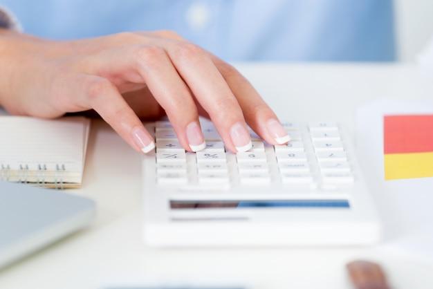 Schließen sie herauf geschäftsfrauhand unter verwendung eines taschenrechners auf schreibtisch mit arbeitsplatz