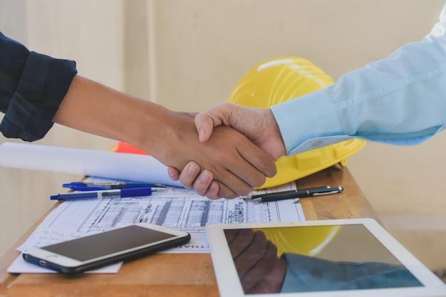 Schließen sie herauf geschäftsleute schütteln handvereinbarungserfolgsarchitekturbauprojekt