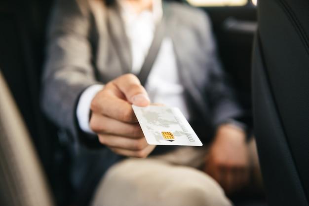 Schließen sie herauf geschäftsmann, der dem fahrer kreditkarte gibt