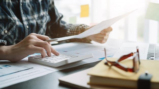 Schließen sie herauf geschäftsmann, der rechner und laptop für die berechnung des finanz-, steuer-, buchhaltungs-, statistik- und analytischen forschungskonzepts verwendet