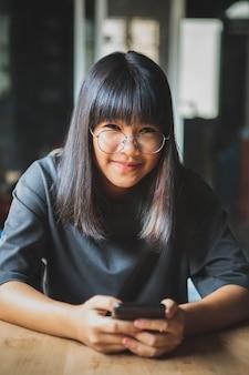 Schließen sie herauf gesicht des lächelnden gesichtes des asiatischen teenagers, das smartphone in der hand hält
