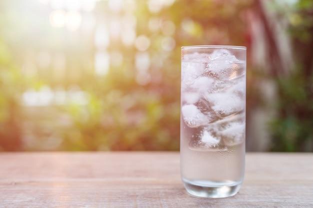 Schließen sie herauf glas kaltes wasser mit eis auf tabelle mit unschärfennatur-gartenhintergrund