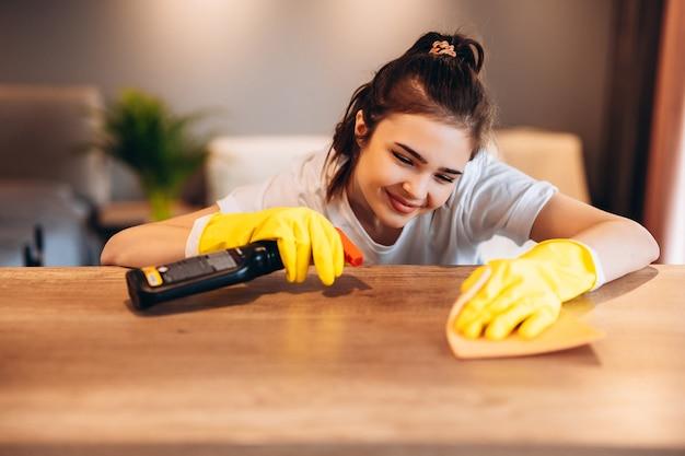 Schließen sie herauf glückliche frau, die tabelle zu hause küche reinigt