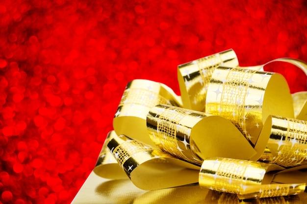 Schließen sie herauf goldenen präsentkarton mit großem bogen an bokeh weißem unschärfehintergrund