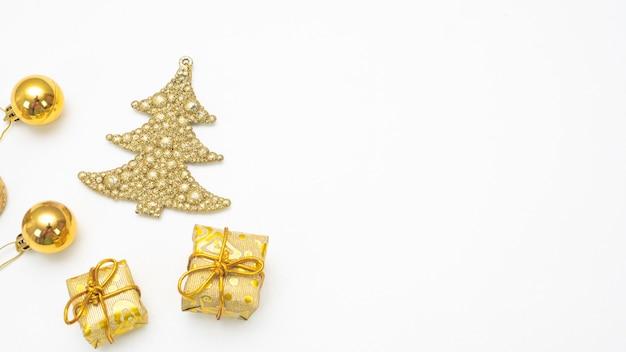 Schließen sie herauf goldenes weihnachtszubehör auf draufsichtkopienraum des weißen hintergrundes